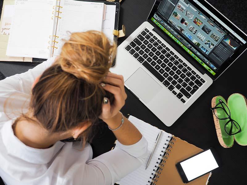 Chica agobiada con sus preocupaciones mientras trabaja con el ordenador. Foto de Pexels