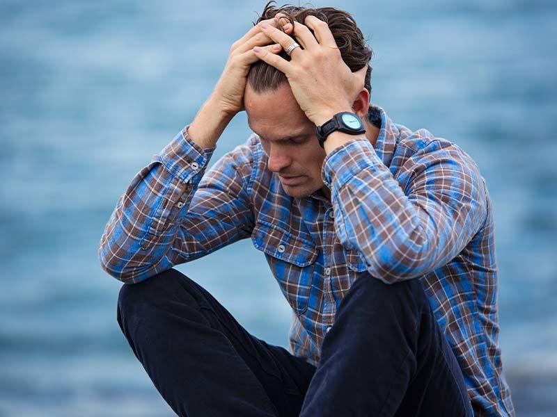 Un hombre reflexionando sobre sus preocupaciones que le acecha. Foto de Pexels.
