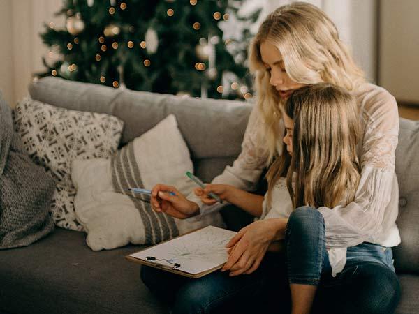 Madre e hija dibujando un árbol de Navidad en la carta para los Reyes Magos