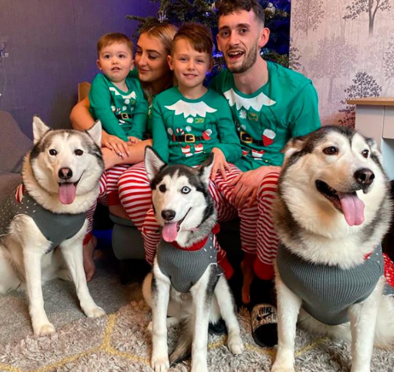 El bebé, Parker, y la perrita, Millie, junto a su familia. Los dos padres, el hermano mayor de Parker y dos perros de raza Husky más.