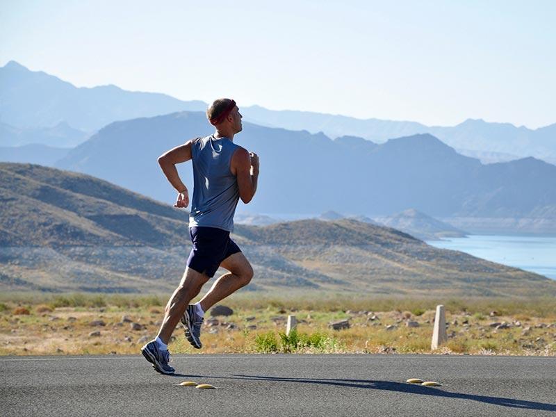 Hombre corriendo por una carretera tranquila.