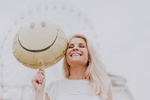 mujer con globo sonriendo sentirse bien consigo mismo