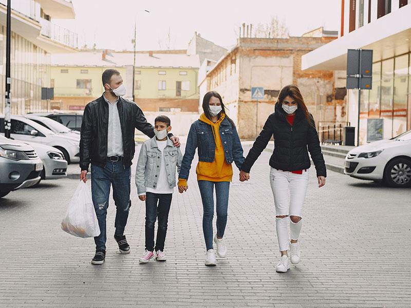 Una familia paseando con mascarilla cumpliendo las normas de seguridad. Foto de Pexels.