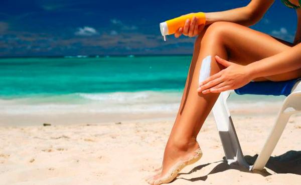 Mujer echándose protector solar Cómo ponerte morena