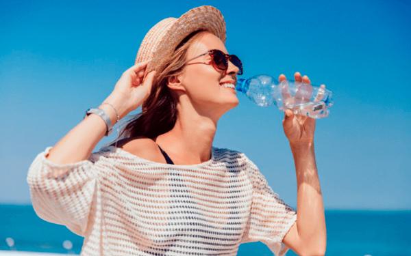 Mujer bebiendo agua al sol