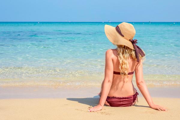 Mujer con un sombrero tomando el sol Cómo ponerte morena